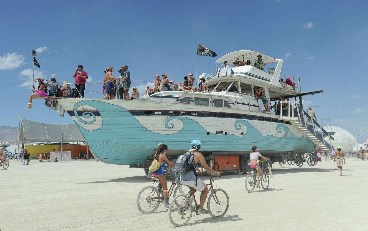 An old wooden yacht art car rolls through the playa.