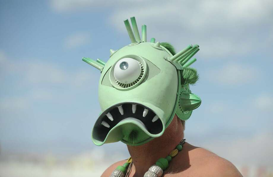 A man with a creature mask walks the playa. Photo: AP