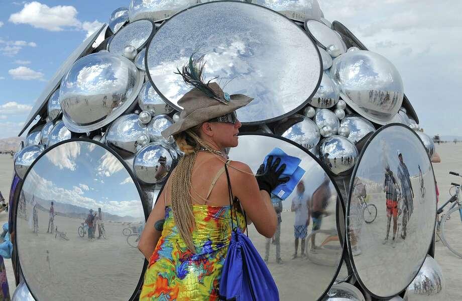 Artist Kirsten Berg cleans her art work on the playa. Photo: AP