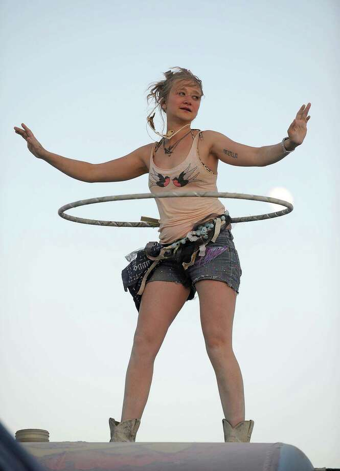 A young women hula hoops on top of a bus while a band plays music next to her on Tuesday. Photo: AP