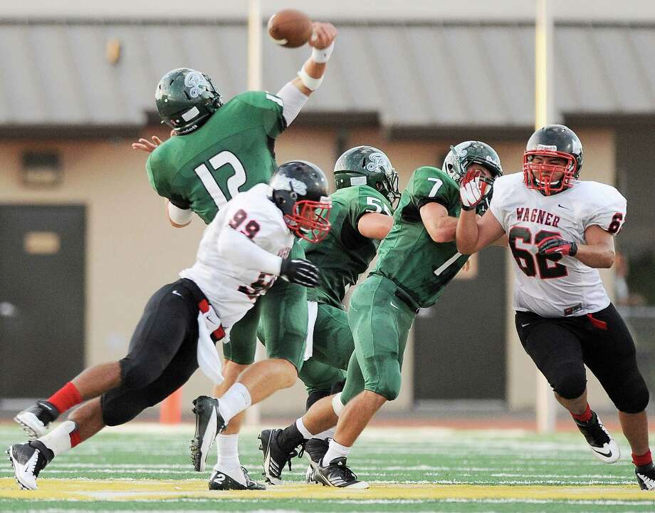 Reagan quarterback Kyle Keller (12) loses the ball as he is hit by Wagner's Cory Ward (99) in the first half of a high school football game, Saturday, Sept. 1, 2012, at Comalander Stadium in San Antonio. Photo: Darren Abate, Express-News