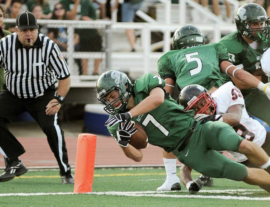 Reagan's Marshall Young (7) runs for a touchdown as he is brought down by Wagner's Adeo Davis (59) in the first half of a high school football game, Saturday, Sept. 1, 2012, at Comalander Stadium in San Antonio. Photo: Darren Abate, Express-News