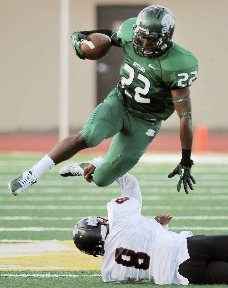 Reagan's Elijah Ball (22) evades Wagner's Chiante Rome in the first half of a high school football game, Saturday, Sept. 1, 2012, at Comalander Stadium in San Antonio. Photo: Darren Abate, Express-News