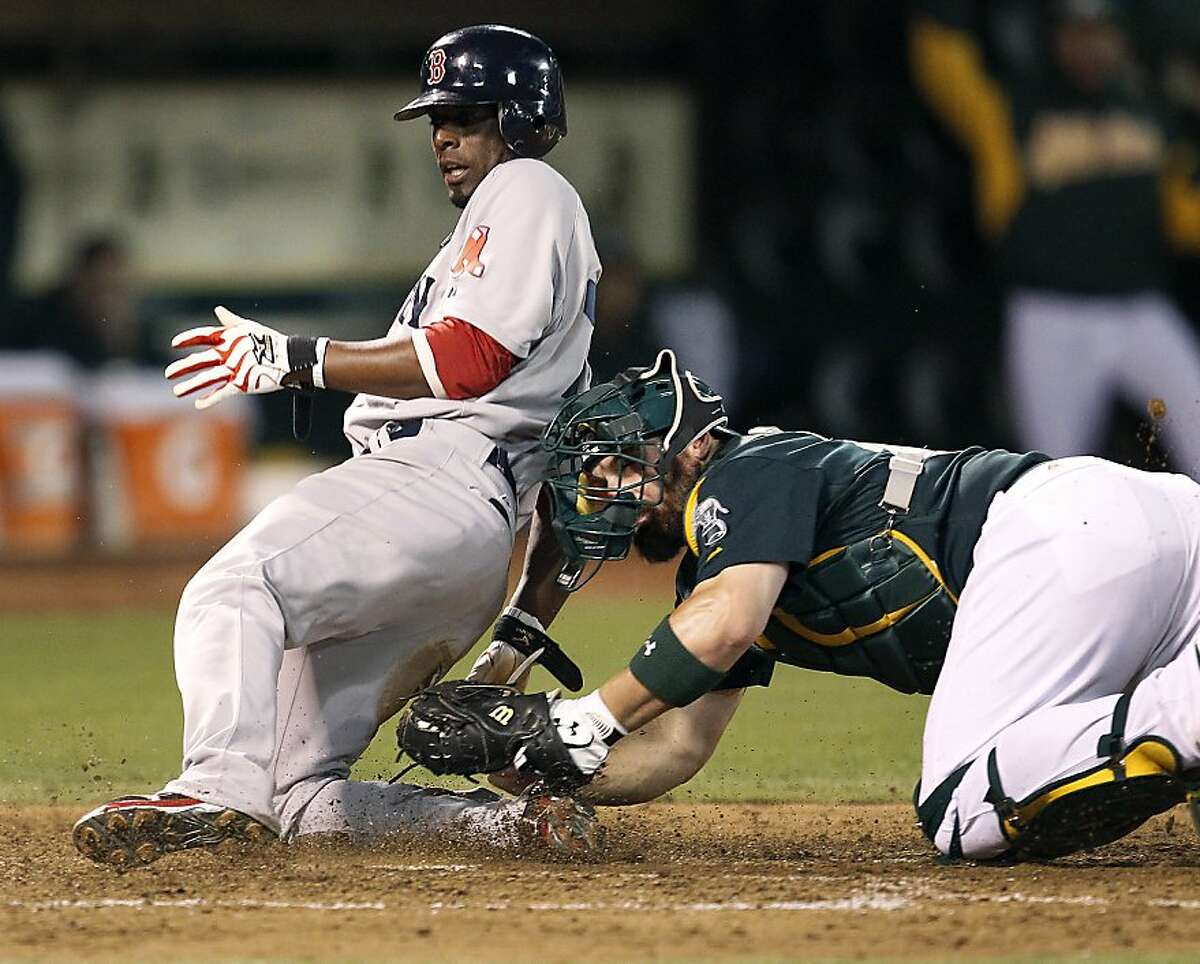 Boston Red Sox' Pedro Ciriaco (77) slides safely into home plate past the tag of Oakland Athletics catcher Derek Norris (36) in the sixth inning of a baseball game Saturday, Sept. 1, 2012 in Oakland, Calif. (AP Photo/ Tony Avelar)