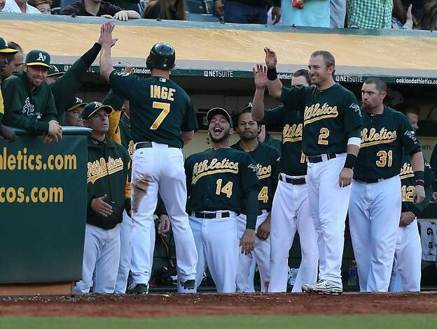 Brandon Inge of the A's celebrates with teammates after he scored in the third inning - likely his final play of 2012. Photo: Jed Jacobsohn, Getty Images