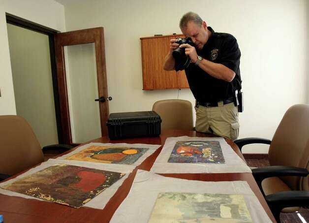 Olmos Park Sr. Sergeant Joe Schutze photographs art work that is said to be by dissident Soviet artist, Yevgeny Rukhin. Photo: Helen L. Montoya, San Antonio Express-News / ©SAN ANTONIO EXPRESS-NEWS