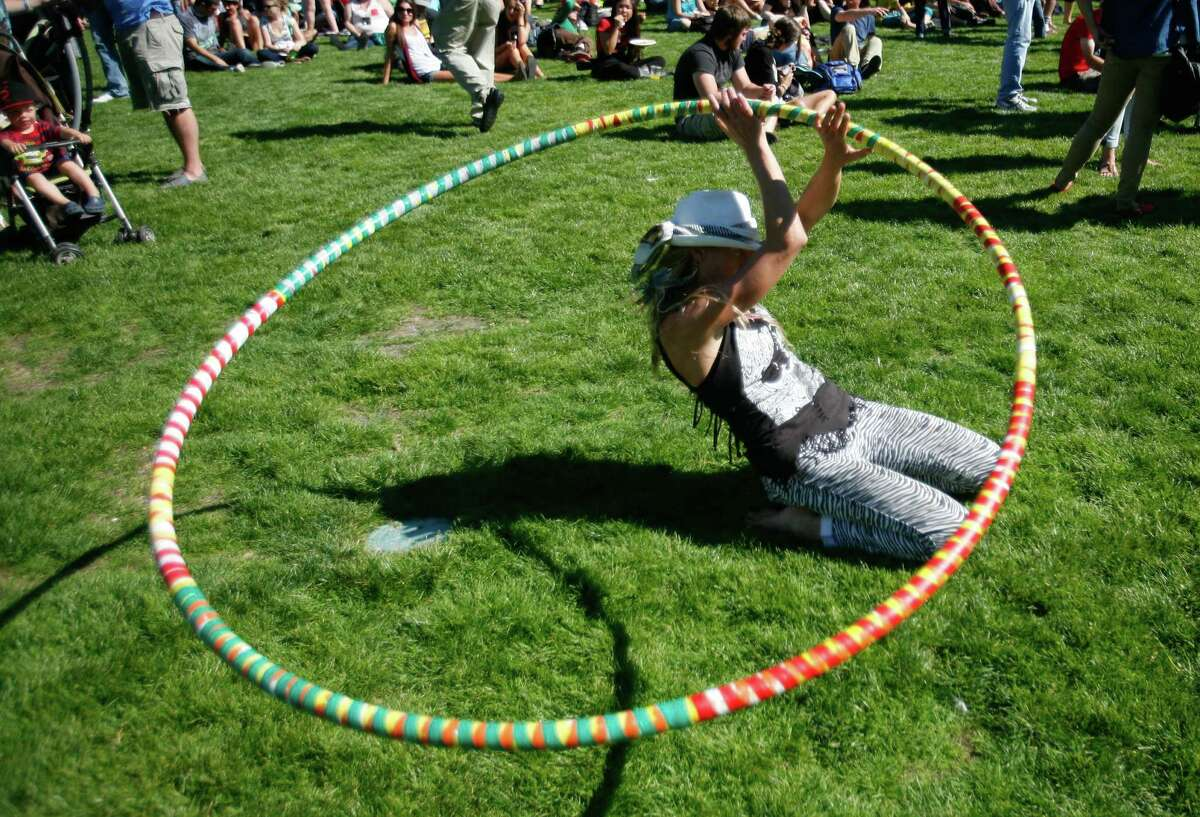 A woman dances with a hula hoop.
