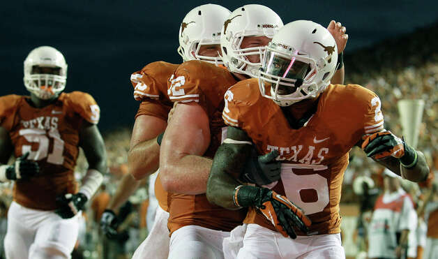 D.J. Monroe checks to see the extent of his lineman piling on to congratulate him after a touchdown as Texas hosts Wyoming at D.K.Royal Stadium in Austin on September 1, 2012. Photo: Tom Reel, Express-News / ©2012 San Antono Express-News