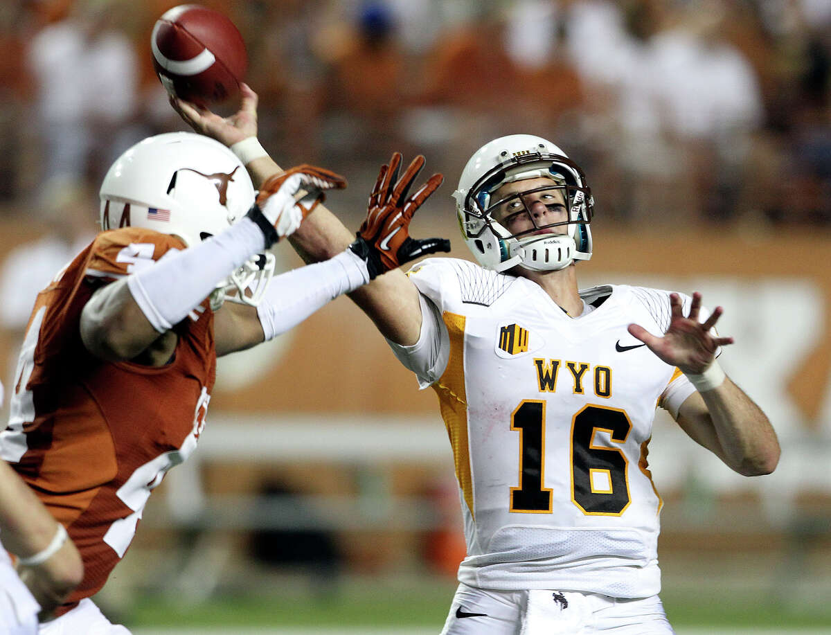 Brett Smith is pressured by Jackson Jeffcoat as Texas hosts Wyoming at D.K.Royal Stadium in Austin on September 1, 2012.