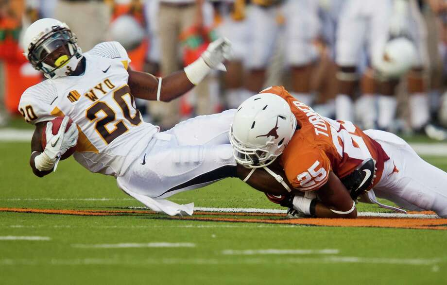 Texas' Josh Turner wraps up Wyoming's Blair Burns. Photo: Ricardo Brazziell / Austin American-Statesman