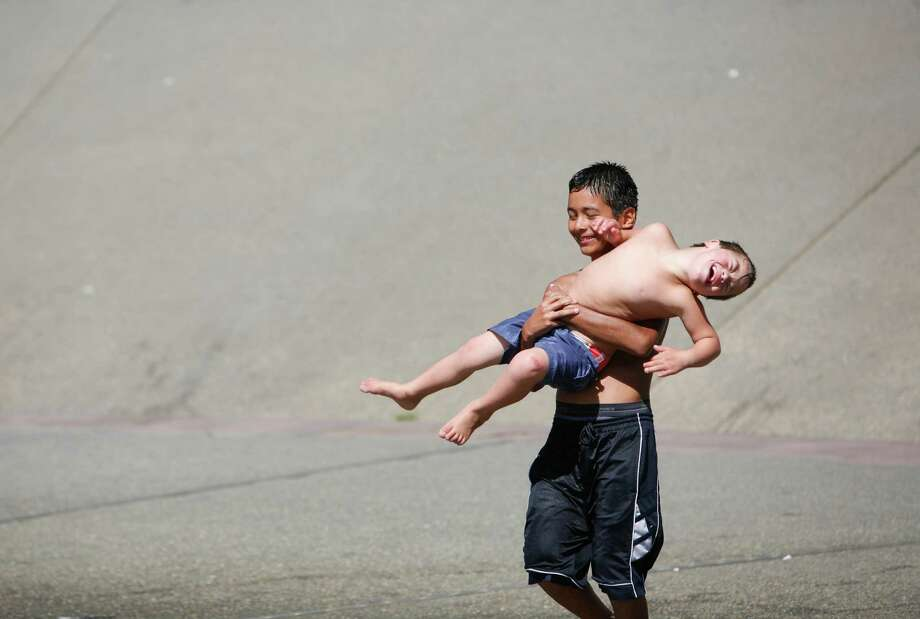 A boy picks up Diego Gardner-Garcia as he walks towards the fountain. Photo: Sofia Jaramillo / SEATTLEPI.COM