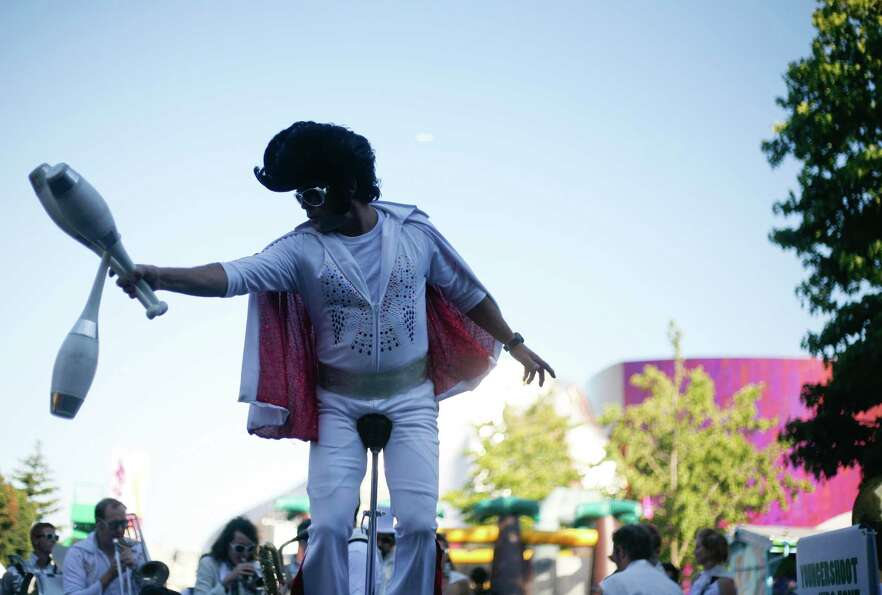 A man dressed as Elvis juggles bowling pins while riding a unicycle.