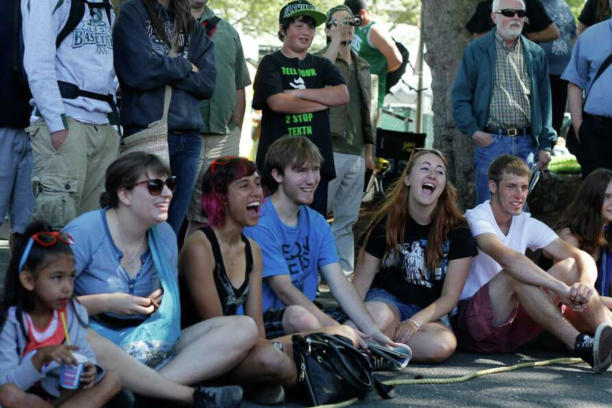 A crowd watching a street performer laughs out loud.