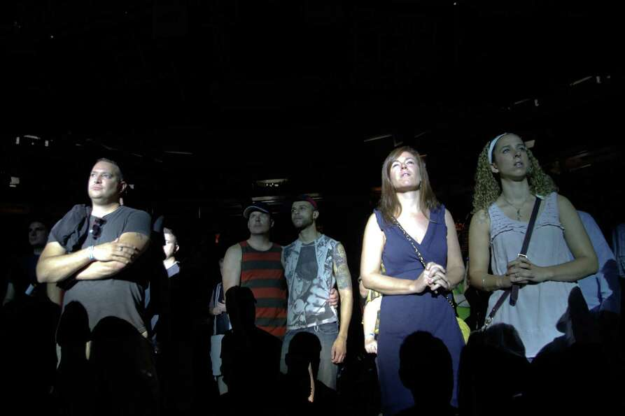 People watch as Gotye performs live inside KeyArena.