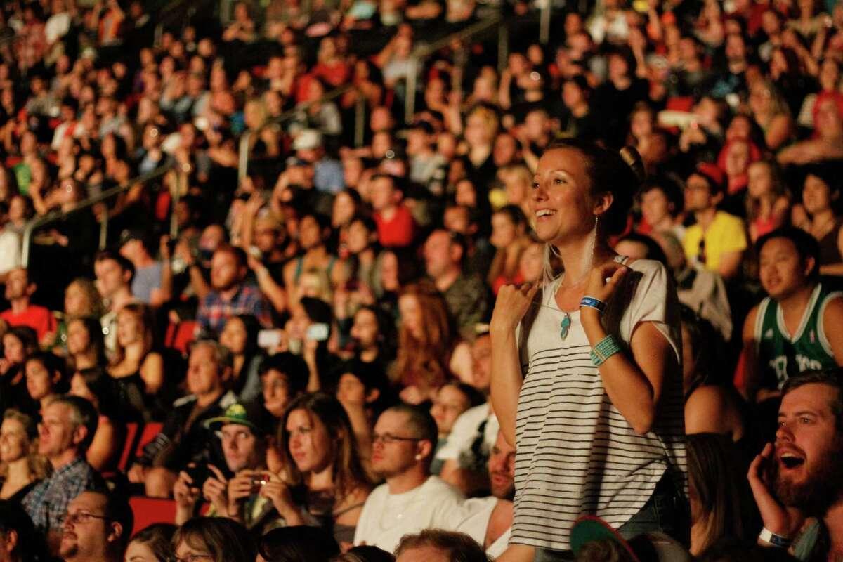 A woman watches the band Gotye at KeyArena.