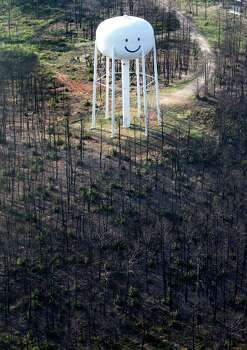 As the one-year anniversary of the The Bastrop Fire Complex fire that burned much of Bastrop State Park and the so-called Lost Pines area of central Texas approaches, the much-photographed smiling water tower East of Bastrop is still surrounded by dead trees as seen in this Monday Aug 20, 2012 aerial image. Photo: William Luther, San Antonio Express-News / © 2012 San Antonio Express-News