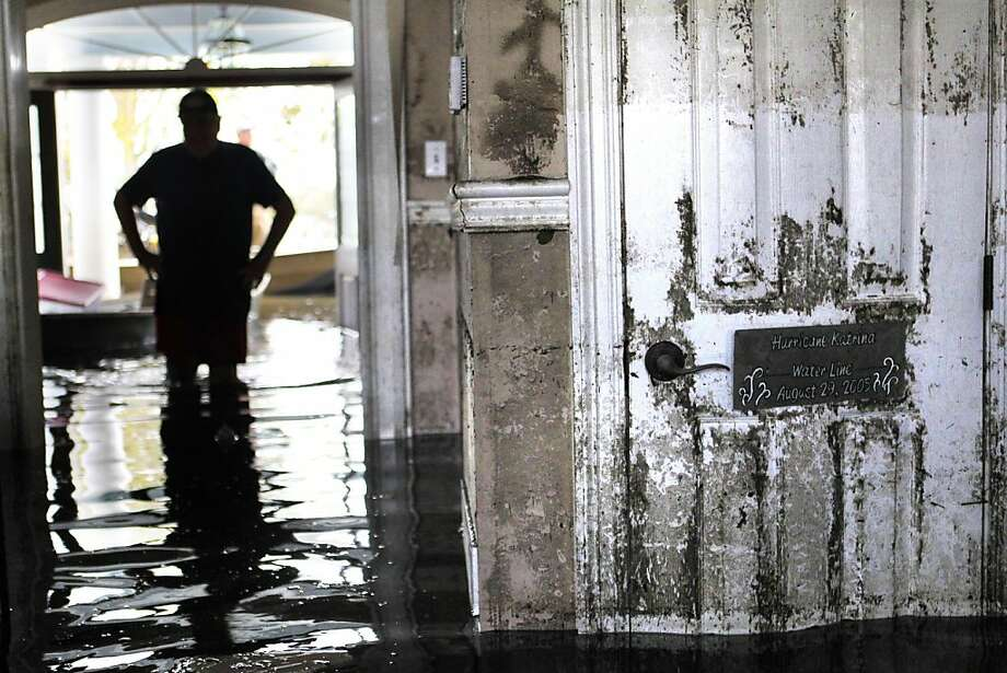 Don Duplantier walks through his flooded home as water recedes in Braithwaite, La. In the foreground is a sign marking the waterline from Hurricane Katrina, but floodwater from Hurricane Isaac reached the second floor. Photo: Gerald Herbert, Associated Press