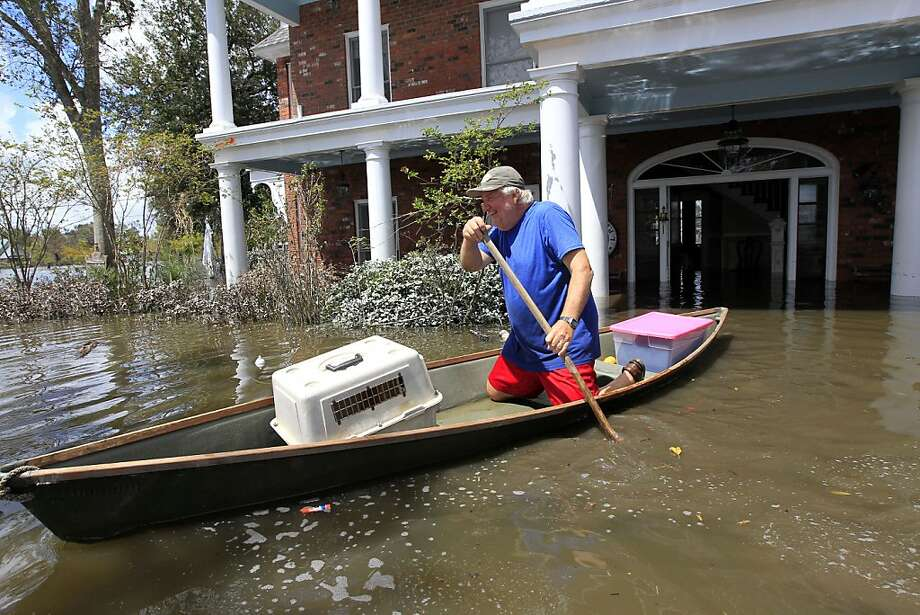 Don Duplantier paddles a pirogue from his flooded home as floodwaters from Hurricane Isaac recede in Braithwaite, La., Sunday, Sept. 2, 2012. Duplantier had retrieved his cat and had collected his daughter's bridesmaid dress for the upcoming wedding of his son. (AP Photo/Gerald Herbert) Photo: Gerald Herbert, Associated Press