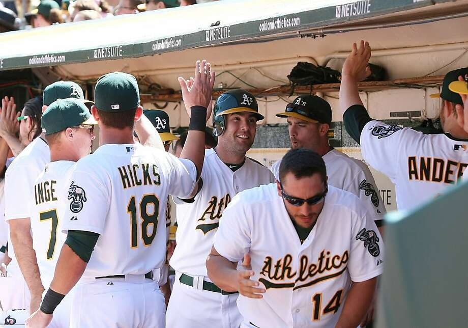 Seth Smith gets congratulated after scoring on a single by Stephen Drew to give the A's a 5-0 lead in the third. Photo: Tony Medina, Getty Images