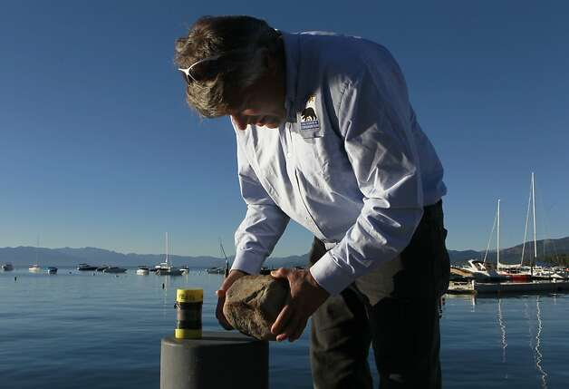 Gordon Seitz, from the California Geological Survey, examines a rock estimated to be 12,000 years old, in Tahoe City, Calif. on Wednesday, Aug. 29, 2012. Seitz says the rock, which was recovered from the floor of Lake Tahoe during a seismic study, was probably deposited there by a glacier. Photo: Paul Chinn, The Chronicle