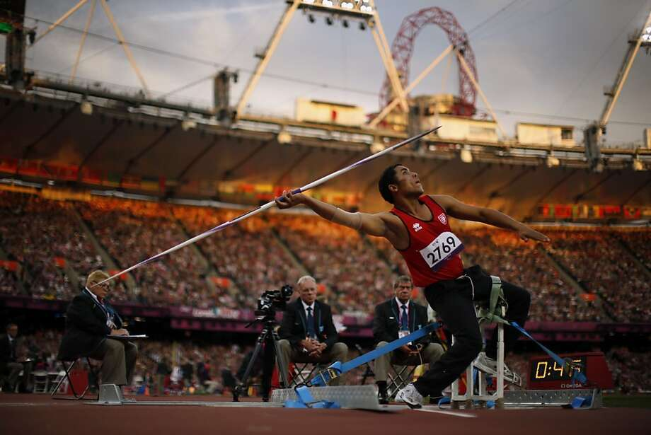 In light from the setting sun, Tunisia's Mohamed Ali Krid makes a throw in the men's javelin F34 category event during the athletics competition at the 2012 Paralympics, Saturday, Sept. 1, 2012, in London.  (AP Photo/Matt Dunham) Photo: Matt Dunham, Associated Press