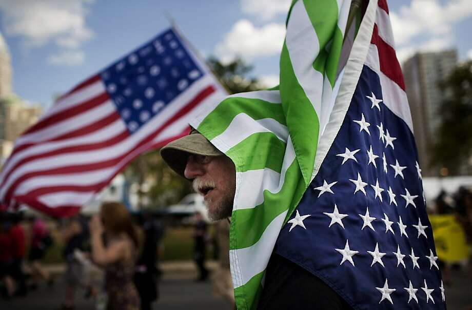 A protestor marches with a U.S. flag over his head during a demonstration in Charlotte, North Carolina, U.S., on Sunday, Sept. 2, 2012. Demonstrators marched through Charlotte's central business district ahead of the Democratic National Convention (DNC) to protest corporate influence on politics. Photographer: Victor J. Blue/Bloomberg Photo: Victor J. Blue, Bloomberg