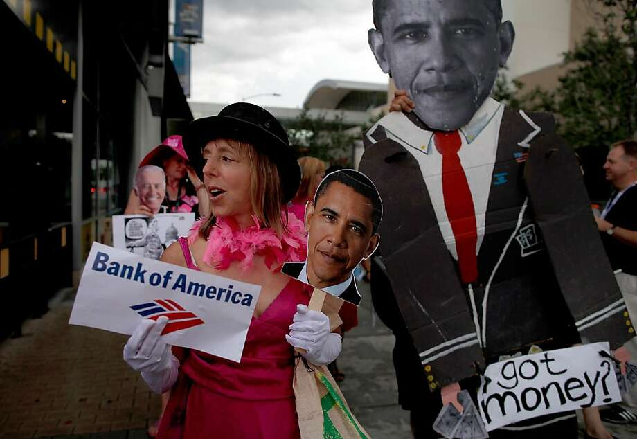 Medea Benjamin of Code Pink carries signs in front of the NASCAR Hall of Fame. Photo: Tom Pennington, Getty Images