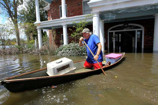 Don Duplantier paddles a pirogue from his flooded home as floodwaters from Hurricane Isaac recede in Braithwaite, La., Sunday, Sept. 2, 2012. Duplantier had retrieved his cat and had collected his daughter's bridesmaid dress for the upcoming wedding of his son. (AP Photo/Gerald Herbert) Photo: Gerald Herbert / AP