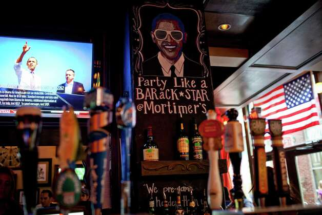 A campaign ad plays in a bar featuring a drawing  of President Barack Obama in downtown Charlotte, N.C., on Sept. 1, 2012. The Democratic National Convention will begin in Charlotte on Tuesday. (Max Whittaker/The New York Times) Photo: MAX WHITTAKER / NYTNS