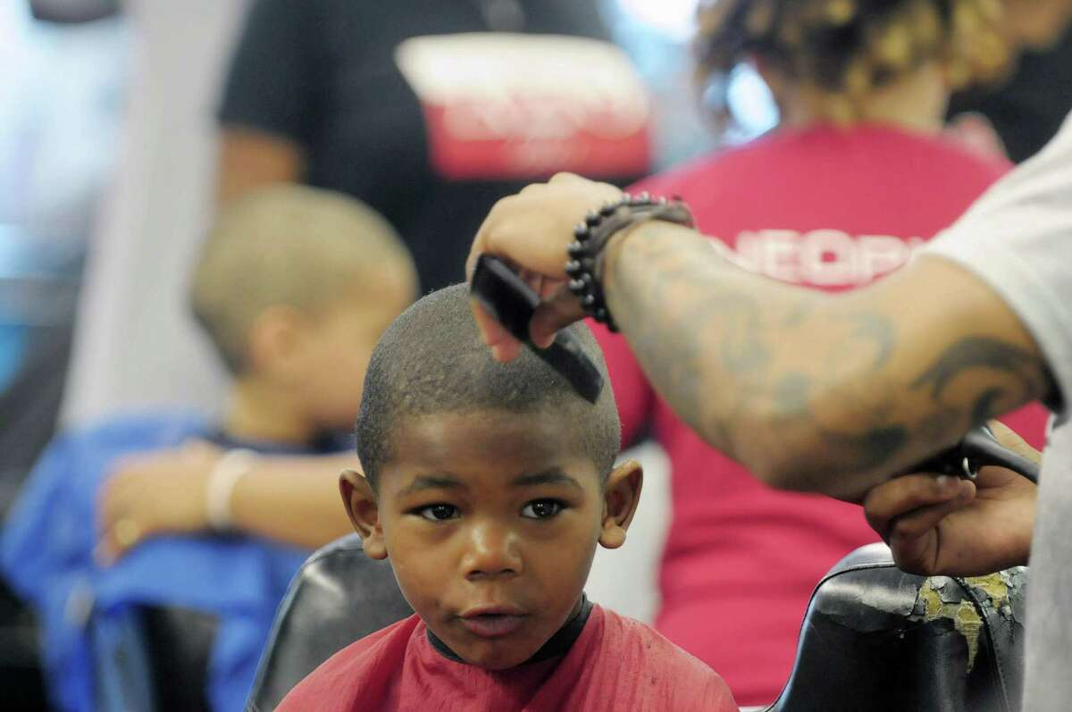 Sae-Hiem Tooley, 5, of Albany gets his haircut during the Community Cuts and Styles event at Bricks Barber Salon on Sunday, Sept. 2, 2012 in Albany, NY. The event this year was organized by the Capital District Chapter of the National Pan-Hellenic Council. The council is composed of nine African American sororities and fraternities. Area children are offered free haircuts and styles and the council pays for the haircuts and styles. Last year over 400 boys and girls received free haircuts or styles through the one day program. Bricks is also part of the Fatherhood Buzz program, which is in eight cities throughout the U.S. The program uses barbers to get out information that would be helpful to fathers. Each quarter the focus of the program changes. This quarter barbers are talking to fathers and passing out information on parenting skills and economic stability. (Paul Buckowski / Times Union)
