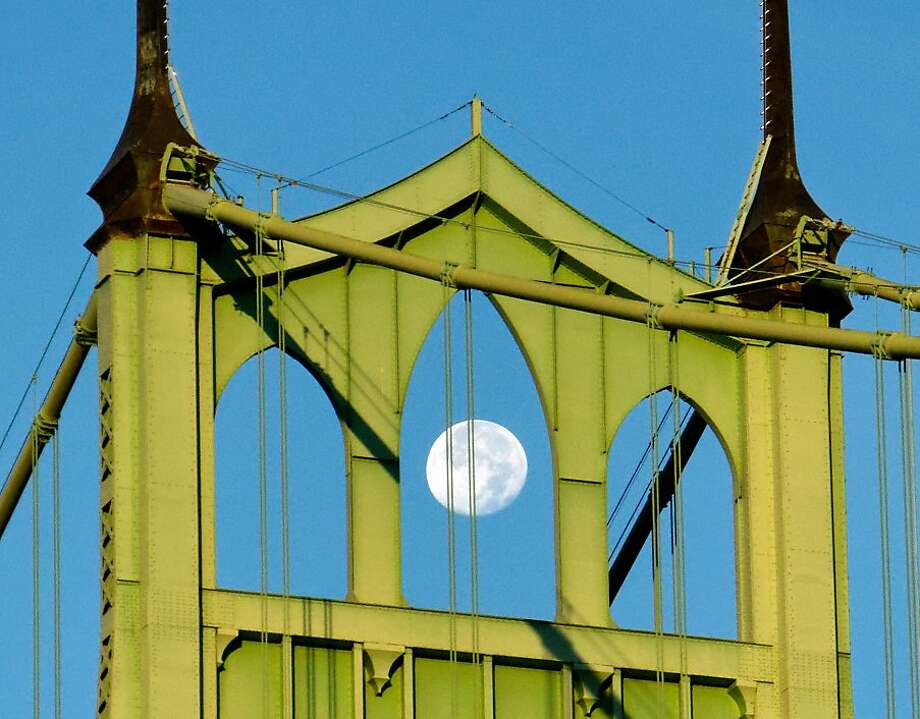 The moon hangs over St. John's Bridge at Cathedral Park, Sunday, Sept. 2, 2012, in Portland, Ore. (AP Photo/The Oregonian, Mike Zacchino) Photo: Mike Zacchino, Associated Press