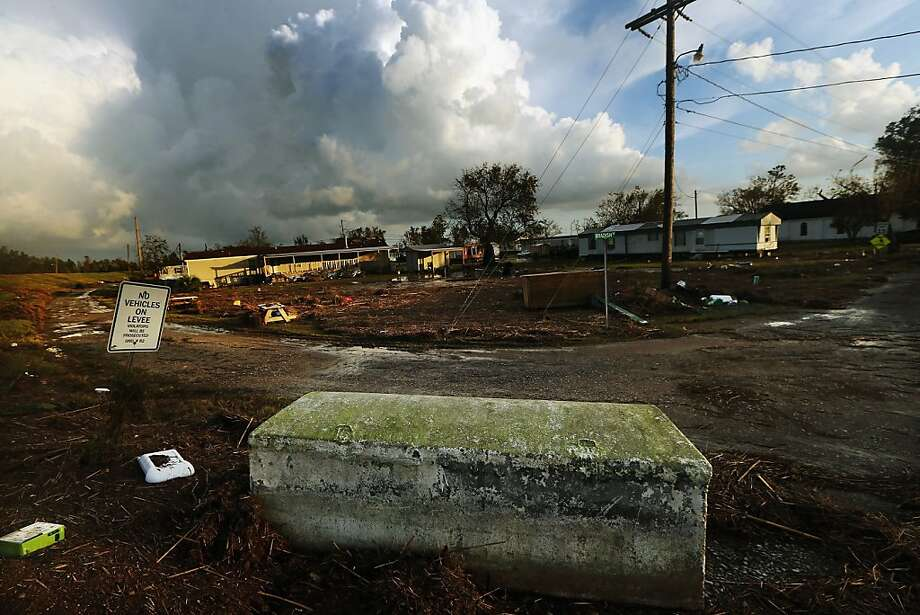 A casket is dislodged from a cemetery and rests on the bottom of a levee in Plaquemines Parish following flooding from Hurricane Isaac on September 2, 2012 in Plaquemines Parish, Louisiana. Today was the first day some residents of lower Plaquemines were allowed to return to assess damage to their homes.    (Photo by Mario Tama/Getty Images) Photo: Mario Tama, Getty Images