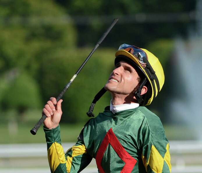 Jockey Ramon Dominguez raises his whip to the sky after he won his sixth race of the day at the Sara