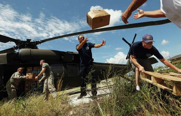 U.S. Army soldiers (L) unload water and MRE's from a Black Hawk helicopter to members of the Boothville-Venice Volunteer Fire Department in lower Plaquemines Parish on September 2, 2012 in Venice, Louisiana. The fire department is providing the necessities to residents who have been largely cut off from the rest of the state by flooding after Hurricane Isaac. Today was the first day some residents of lower Plaquemines were allowed to return to assess damage to their homes. Photo: Mario Tama, Getty Images / 2012 Getty Images