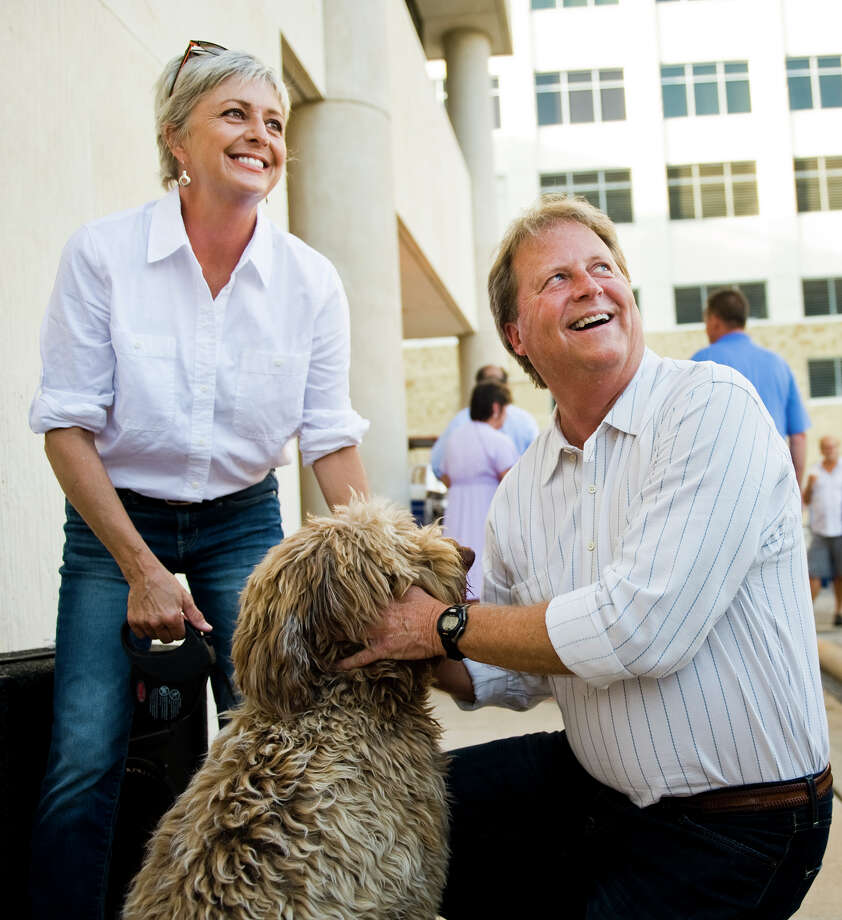 U.S. Senate candidate Paul Sadler (D), right, and his wife, Sherri, left, share a moment with their dog, Murphy, while speaking to supporters during a fish fry at the American Federation of Labor - Congress of Industrial Organizations in Austin, TX on Fri., Aug. 31, 2012.