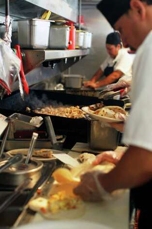 Breakfast tacos are prepared on the line at Taco Taco San Antonio, September 1, 2012. (JENNIFER WHITNEY) Photo: JENNIFER WHITNEY, Special To The Express-News / © Jennifer Whitney