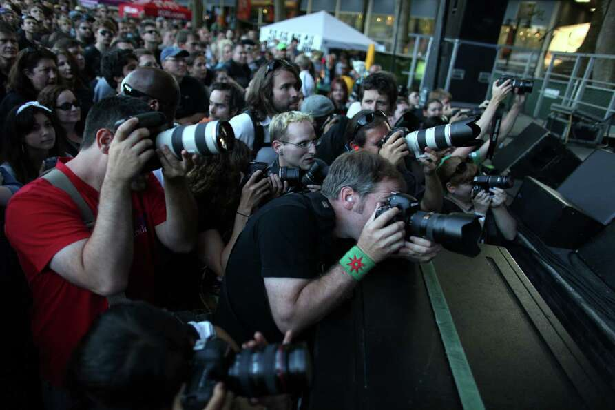 Photographers gather at the base of the Sub Pop Stage during a performance by Mudhoney at Bumbershoo