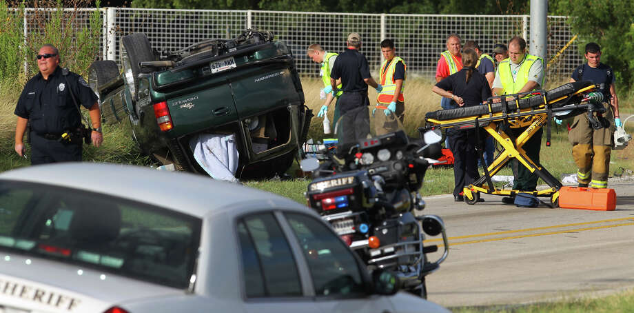 Law enforcement and emergency personnel work at the scene of a one vehicle rollover on the feeder road of Interstate 10 east near the Trainer Hale exit Photo: John Davenport, San Antonio Express-News / San Antonio Express-News