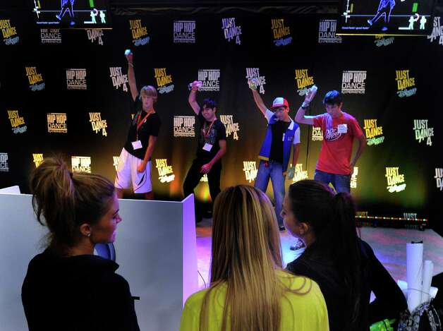 "Expo attendees take to the stage of the ""Just Dance 4"" display. The new game adds a two-player Battle Mode. Photo: Billy Calzada, San Antonio Express-News / © San Antonio Express-News"