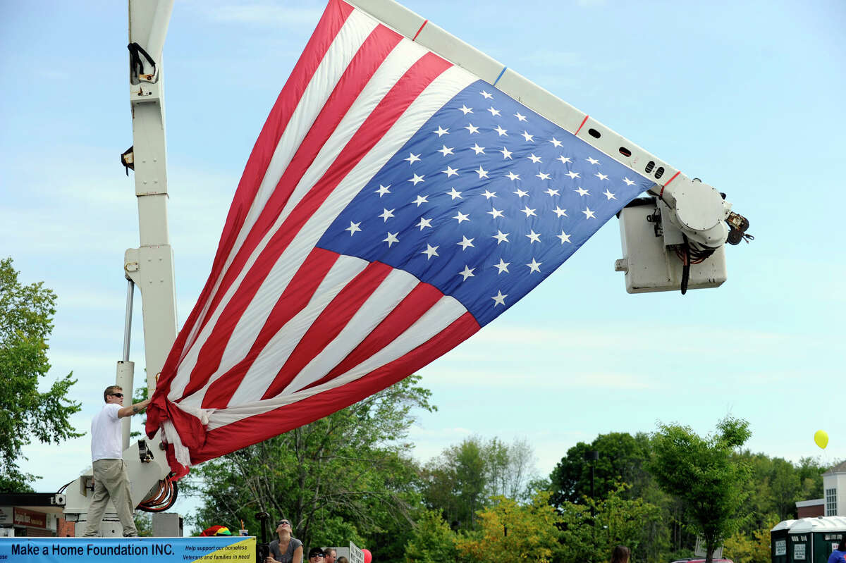 Mike Cunningham, of Newtown, with Make A Home Foundation and Yacko & Sons, hoists a huge American Flag over Queen Street in Newtown for The Labor Day Parade, Monday, Sept. 3, 2012.