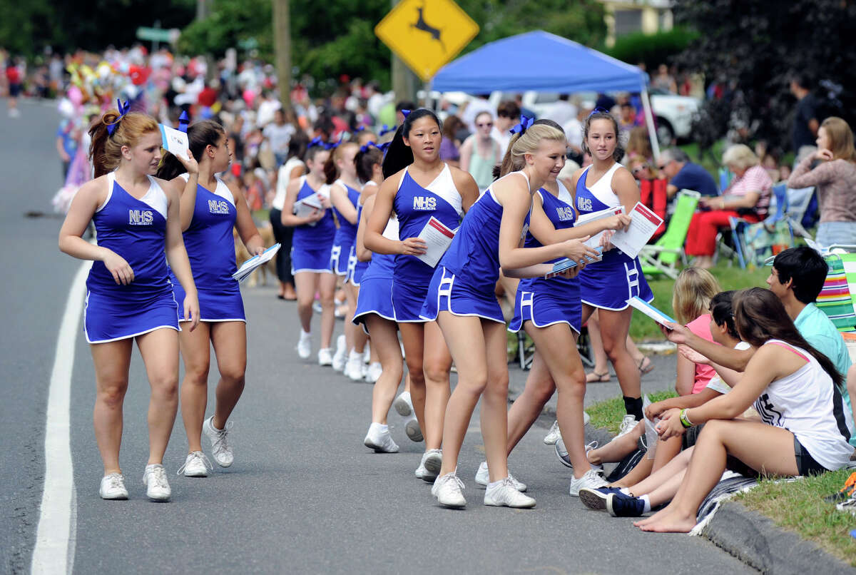 Newtown High School Cheerleaders distribute parade programs to spectators along the route of the Labor Day Parade in Newtown, Monday, Sept. 3, 2012.