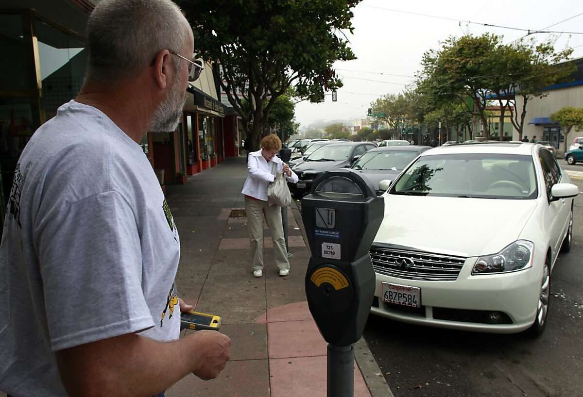 Brad Morisoli (left) and Gwen Kelley try to figure out how to use the pay-by-phone feature for parking meters on West Portal Avenue in San Francisco, Calif. on Monday, Sept. 3, 2012. Officers were issuing parking violations city-wide during the Labor Day holiday.