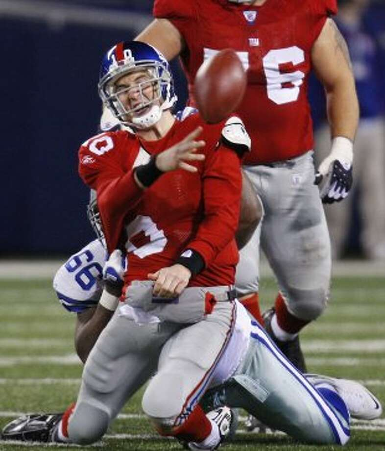 New York Giants quarterback Eli Manning (front) is sacked as he tries to pass the ball by Dallas Cowboys defensive end Chris Canty during the second half of their NFL football game in East Rutherford, New Jersey November 11, 2007. REUTERS/Mike Segar (UNITED STATES) (REUTERS)