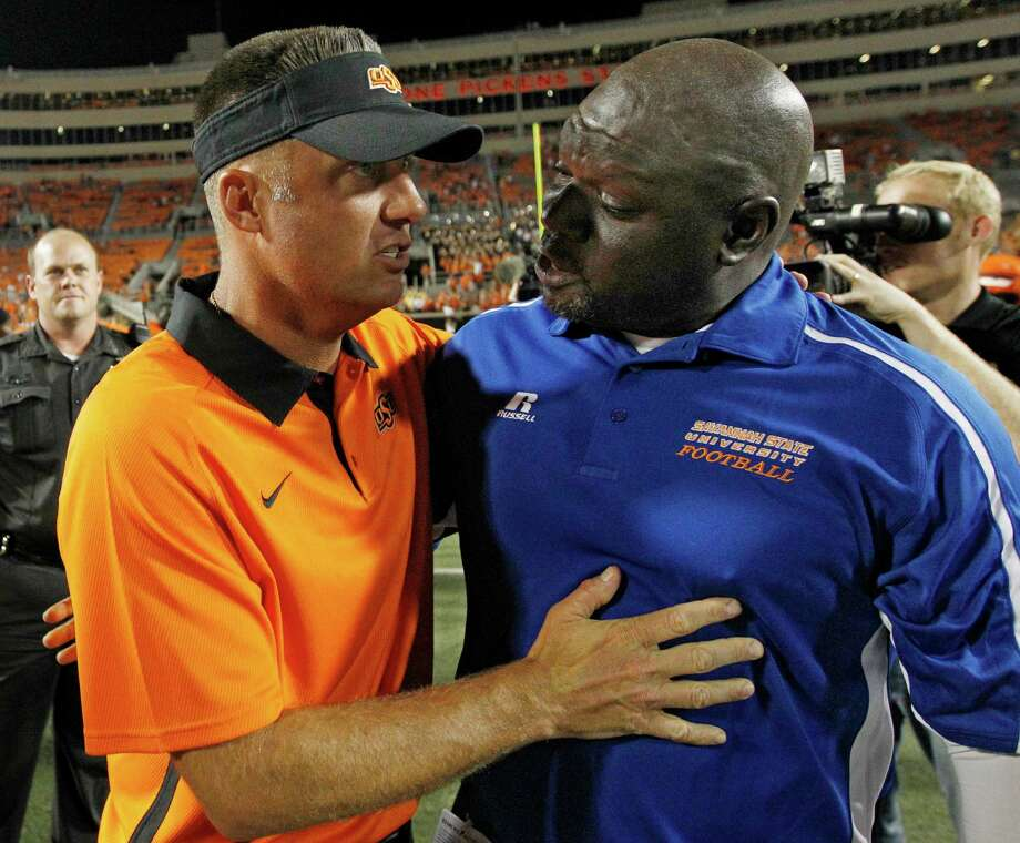 Oklahoma State coach Mike Gundy (left) chats with Savannah State coach Steve Davenport after the Cowboys' 84-0 win Saturday. Photo: Sue Ogrocki, Associated Press / AP