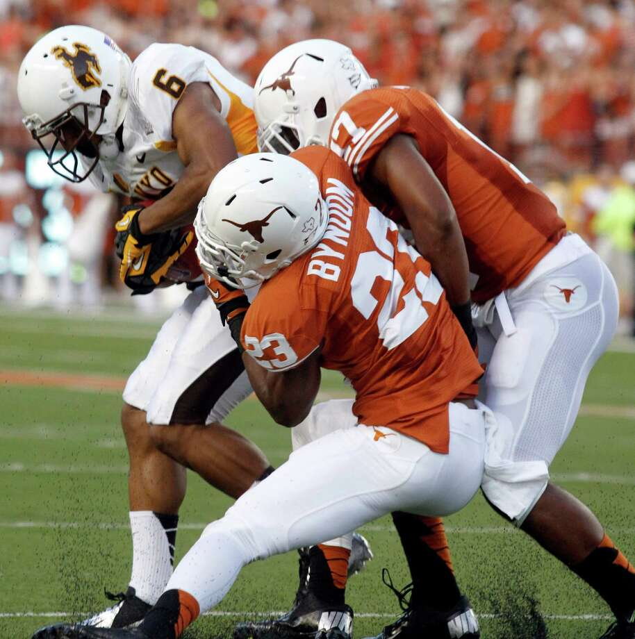 Wyoming's Robert Herron (6) works his way free from Texas defenders Carrington Byndom (23) and Adrian Phillips during the first quarter of an NCAA college football game, Saturday, Sept. 1, 2012, in Austin, Texas.(AP Photo/Jack Plunkett) Photo: Jack Plunkett, Associated Press / FR59553 AP
