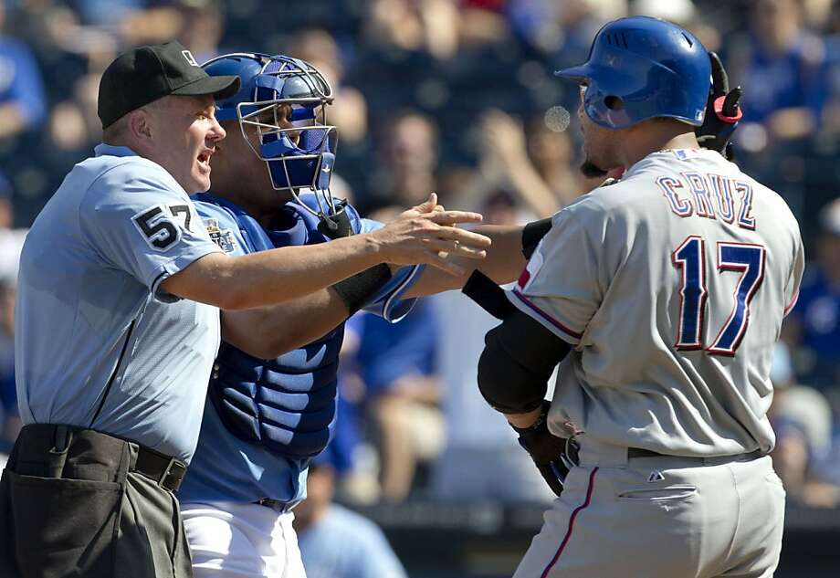 Home plate umpire Mike Everitt (57) steps between Kansas City Royals catcher Brayan Pena and Texas Rangers' Nelson Cruz (17) during the eighth inning. Photo: Orlin Wagner, Associated Press