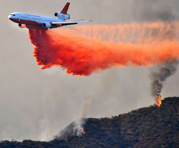 In this Sunday, Sept. 2, 2012 photo, a DC-10 tanker drops fire retardant on a ridge line at fire abo
