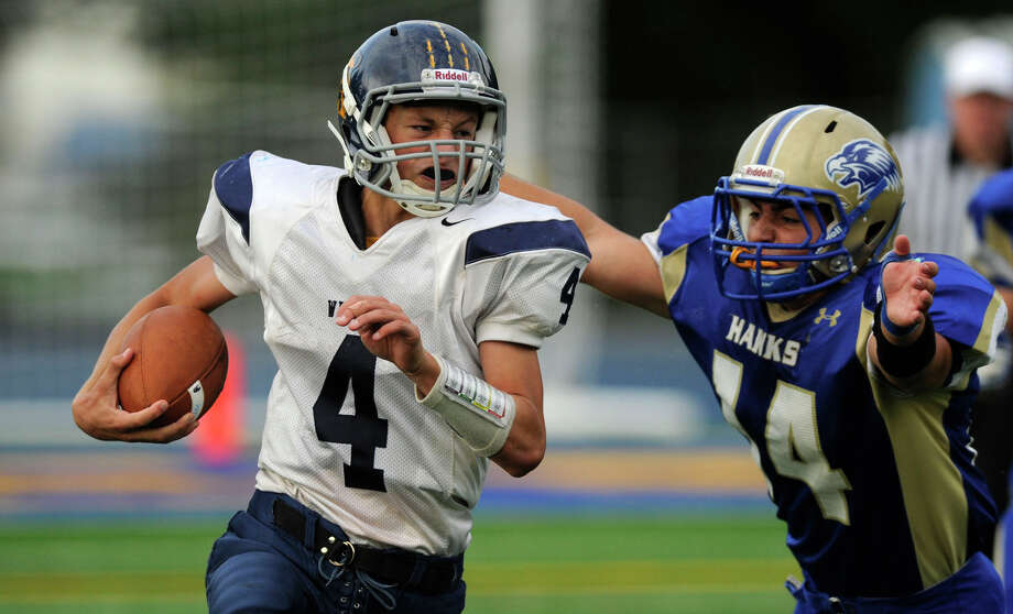 Weston quarterback Tyler Hassett, left, is chased by Newtown's Andrew Cebry during their game at Newtown High School on Saturday, Oct. 1, 2011. Newtown beat Weston 41-7. Photo: Jason Rearick / The News-Times