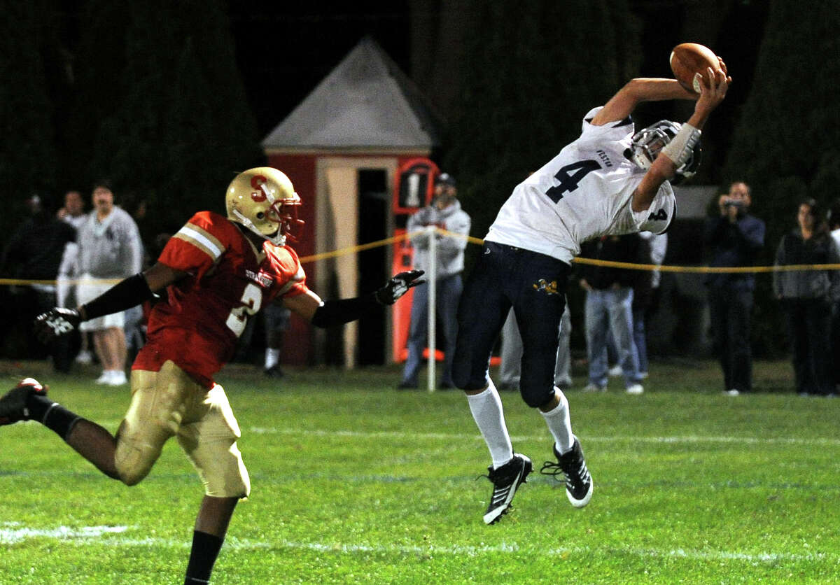 A pass intended for Stratford's #2 Asia Bolling, left, is intercepted by Weston's #4 Tyler Hassett, during boys football action in Stratford, Conn. on Friday September 16, 2011.