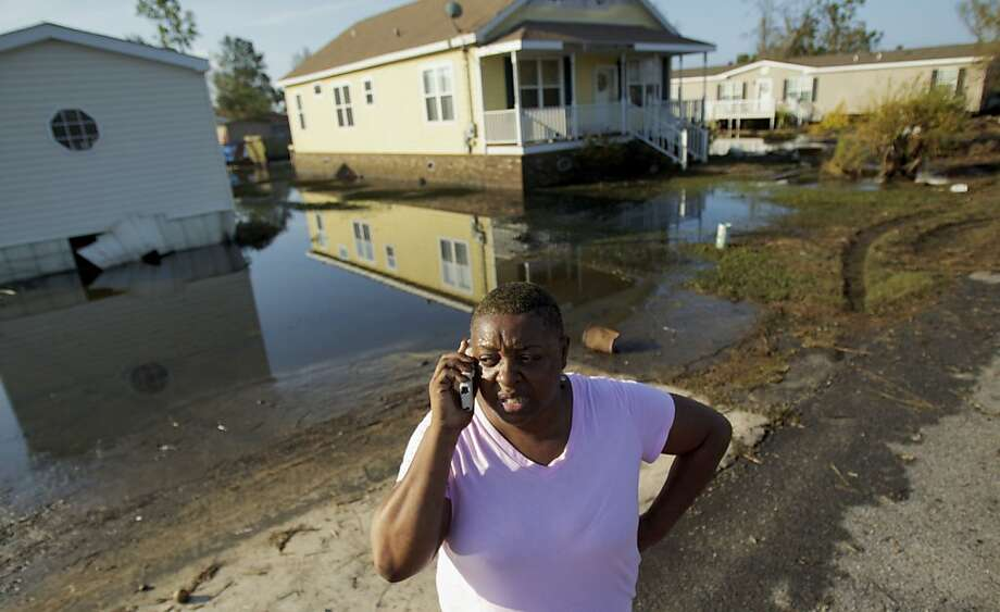 Natachia Riley talks outside the house of her mother, Clara Williams, in Ironton, La., which was flooded from Hurricane Isaac, near Louisiana Hwy 23 in Plaquemines Parish  Monday, Sept. 3, 2012. The house was built seven years ago after mother's previous home was destroyed by Hurricane Katrina. (AP Photo/Matthew Hinton) Photo: Matthew Hinton, Associated Press